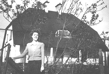 Olive Moore standing in front of the house