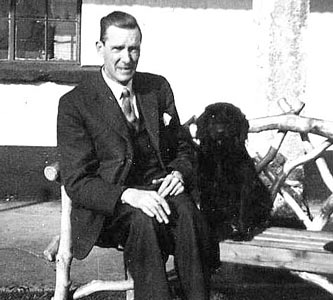 George Moore seated with spaniel, Sandy