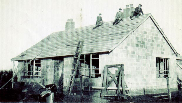 bungalow under construction with figures on the roof