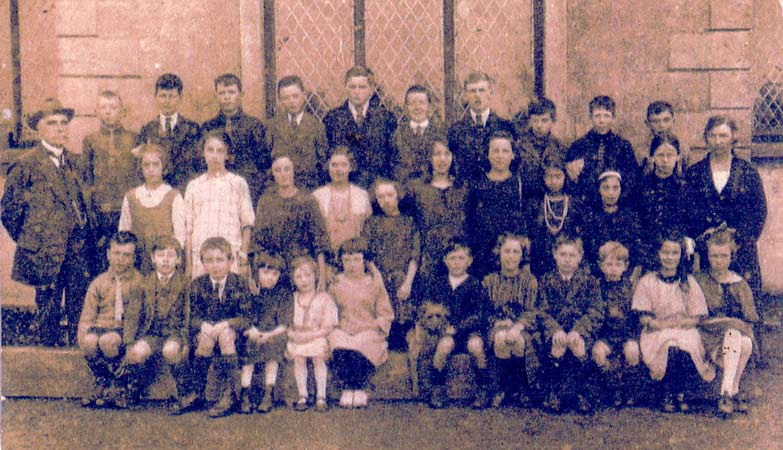 sepia photograph of children in front of school that has diamond pane window